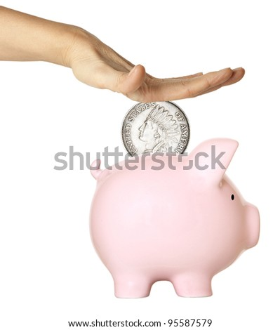 Hand putting coin into the pink piggy bank - stock photo