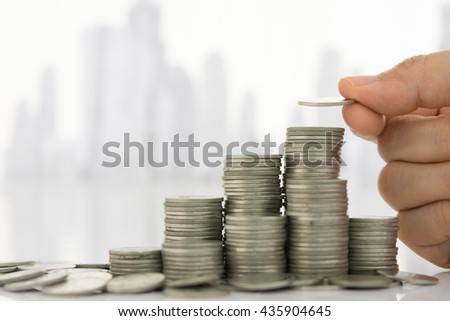 Hand putting  coin on coins stack with city in background. Savings, Finance and Banking, Business Investment Growth Concept.