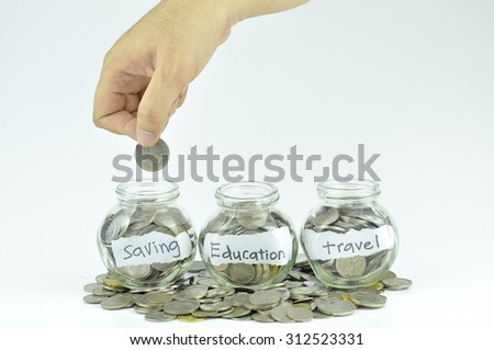 Hand putting coin to the small jar contains coin for travel, education and savings . Selective focus - stock photo