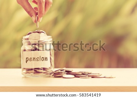 Hand putting Coins in glass jar  for time to money saving for pension concept , vintage retro color tone