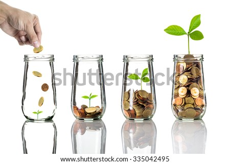Hand putting gold coins into clear bottle on white background,Business investment growth concept - stock photo