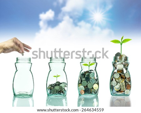 Hand putting mix coins and seed in clear bottle on blurred blue sky with cloud background,Business investment growth concept - stock photo