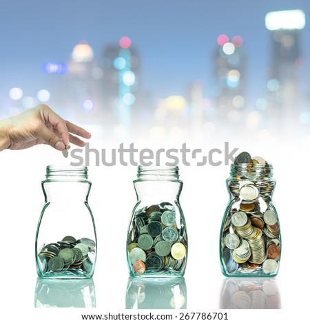 Hand putting mix coins in clear bottle on cityscape photo blurred bokeh background,Business investment growth concept - stock photo