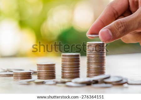 Hand putting money coin stack growing business, Saving money concept