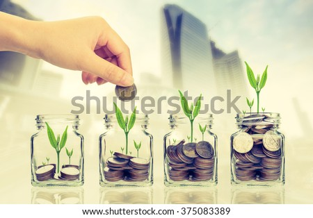 Hand putting money coins and seed in clear bottle on cityscape photo blurred cityscape background,Business investment growth concept - stock photo
