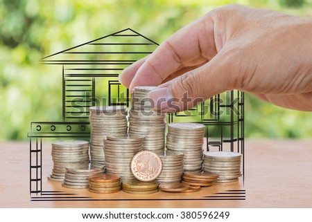 hand putting money coins with  home, Saving for buy home concept - stock photo