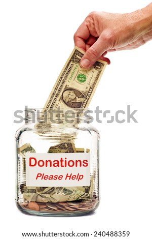 Hand Putting Money In Donation Jar/ Making a Donation - stock photo