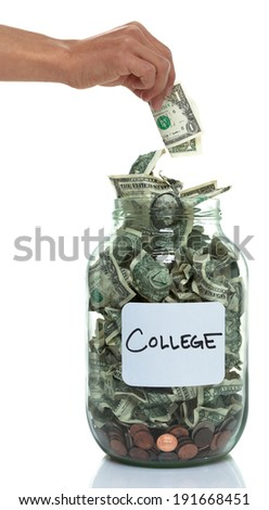 Hand putting money into a savings jar with a white college label - stock photo