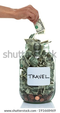 Hand putting money into a savings jar with a white travel label - stock photo