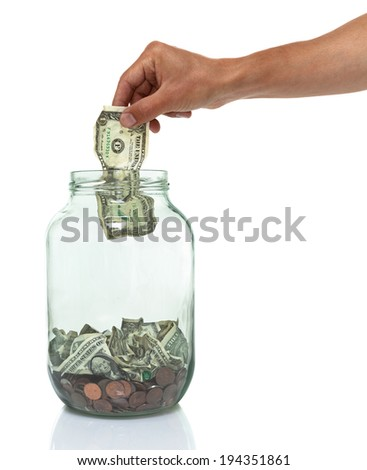 hand putting money into an empty jar - stock photo