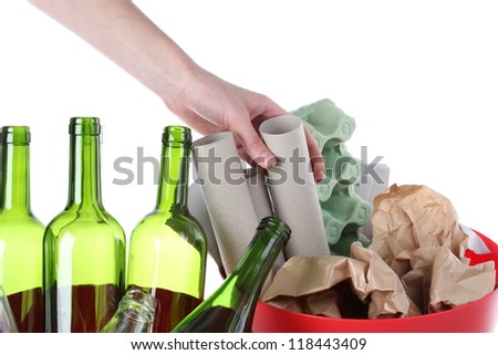 Hand putting paper into recycling bin, isolated background - stock photo