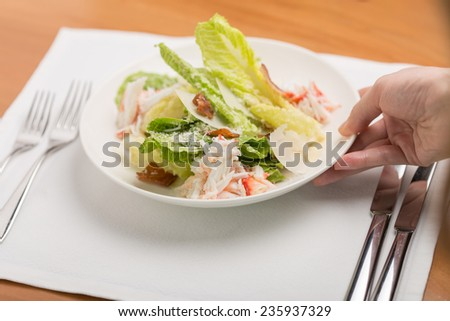 Hand putting plate of crab salad on wooden table - stock photo