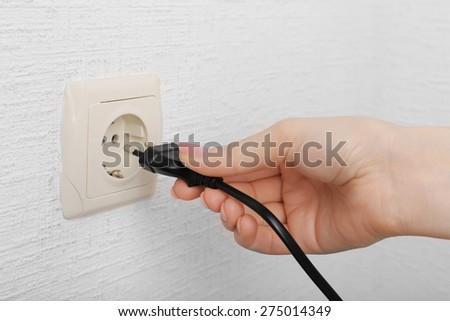 Hand putting plug in electricity socket close up - stock photo