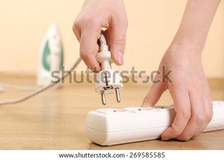 Hand putting plug in extension cord close up - stock photo