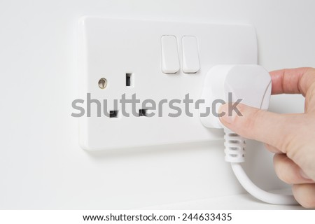Hand Putting Plug Into Electricity Socket - stock photo