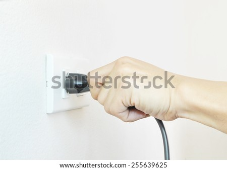 Hand Putting Plug Into Electricity Socket