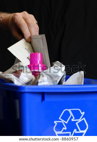 hand putting recycling in bin with plastic and paper - stock photo