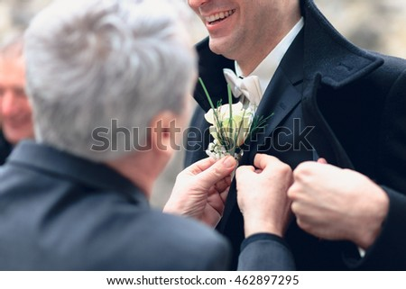 hand putting the boutonniere flower on a groom