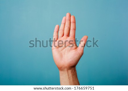 Hand raised against a blue background - stock photo
