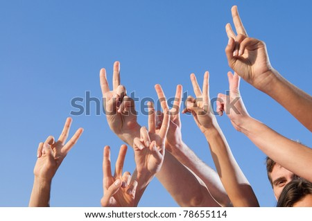 Hand raised with victory sign against blue sky - stock photo
