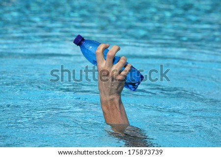 hand raising out of water holding plastic blue bottle of water  - stock photo