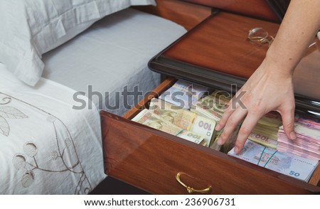 Hand reaches for the money in bedside table filled with Ukrainian cash - stock photo