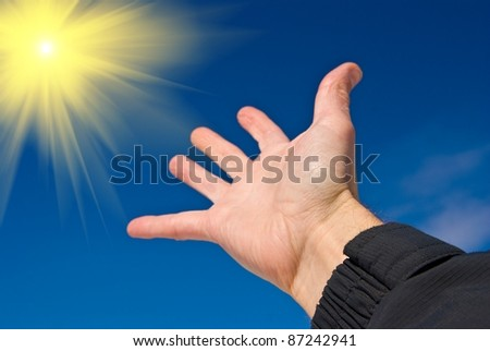 hand reaches for the sun - stock photo