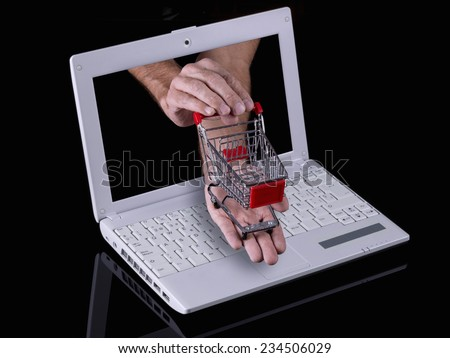 Hand reaches out of a laptop with a shopping cart