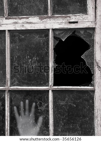 Hand reaches up to touch old dirty Window with focus on smashed pane - stock photo