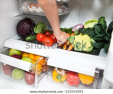 Hand Reaching for Green Apple in Refrigerator Full of Healthy Food Options - stock photo