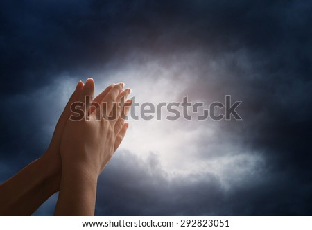 Hand reaching for the  sky with dark stormy clouds - stock photo