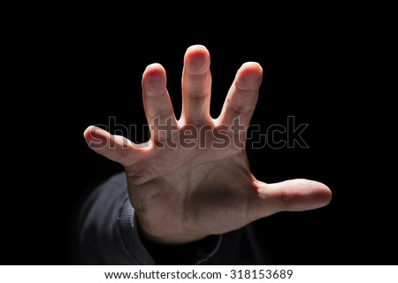 Hand reaching from the dark and grabbing or attacking concept for fear, domestic and child abuse - stock photo