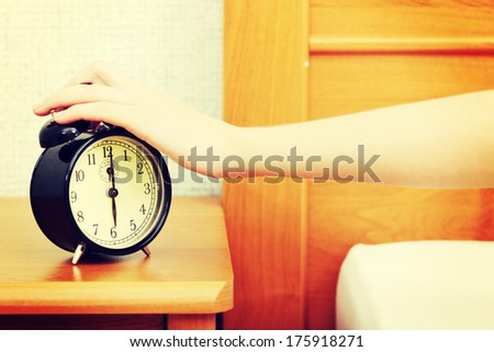 Hand reaching out for alarm clock - stock photo