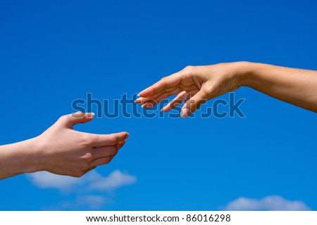 Hand reaching out from the blue sky - stock photo