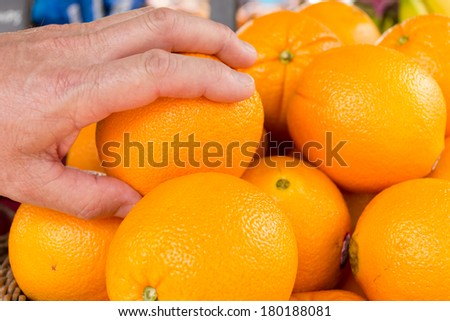 Hand reaching out to pick up fresh juicy oranges from sellers stall. - stock photo
