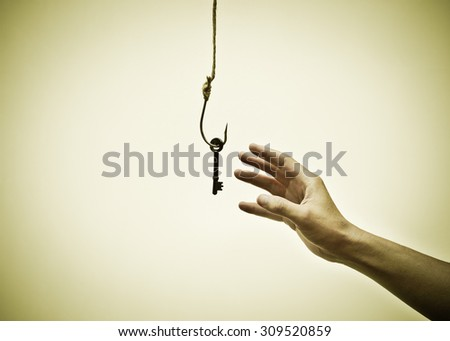 hand reaching out trying to get a key on a fish hook - The victim of success concept - stock photo
