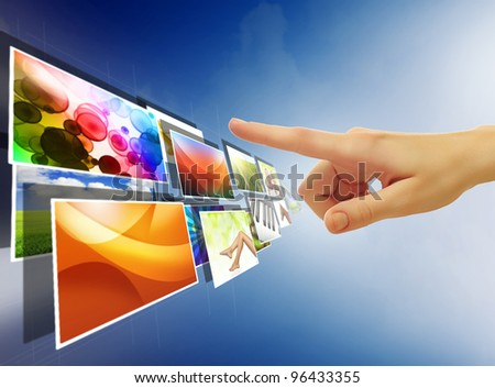 hand reaching with the finger images streaming from the deep over sky blue background - stock photo