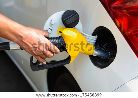 Hand refilling the car with fuel - stock photo