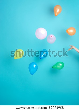 hand releasing colorful balloons on blue background - stock photo