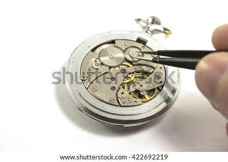 Hand repairs an old mechanical watch. Isolated - stock photo