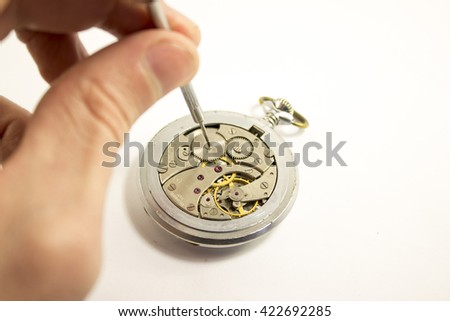 Hand repairs an old watch with white background - stock photo