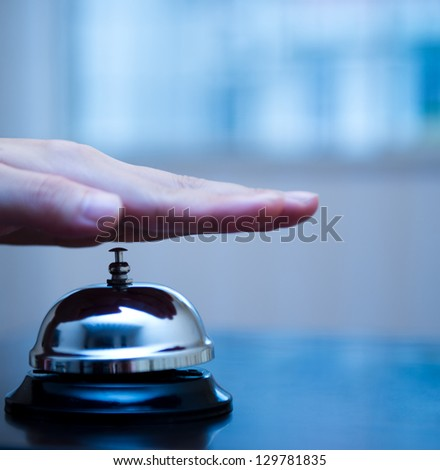 Hand ringing in service bell on wooden table. - stock photo