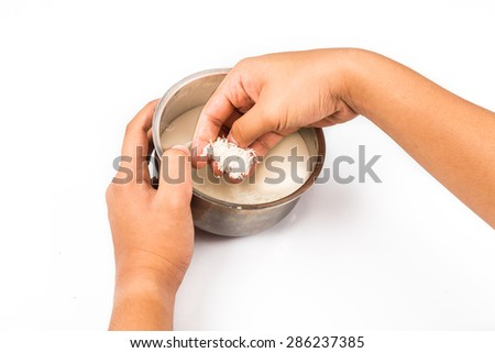 Hand rinsing bowl filled with rice and water.  Rinsed water is natural plant fertilizer. - stock photo