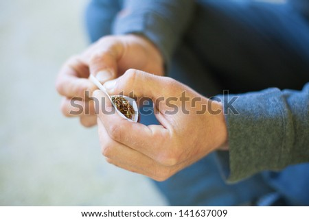 hand rolling marijuana closeup - stock photo