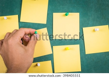 hand's attaching a green thumb stack?Blank Yellow paper, posted ,post-it ,note ,Sticky Note ? - stock photo