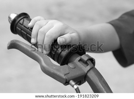 Hand's boy and Bicycle handlebar. black and white , B&W - stock photo