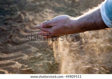 Hand's man throwing dry earth, against the light - stock photo