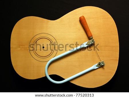 hand saw on guitar wood - stock photo