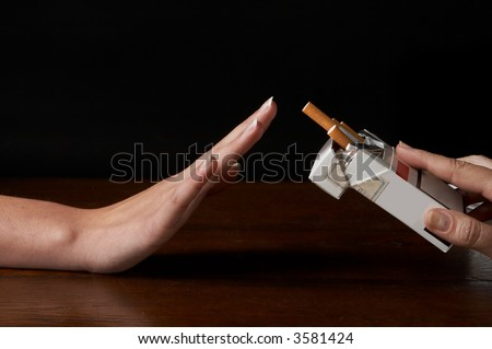 Hand saying no thanks to a packages of cigarettes offered - stock photo