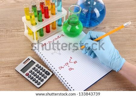 Hand scientist writing formulas - stock photo